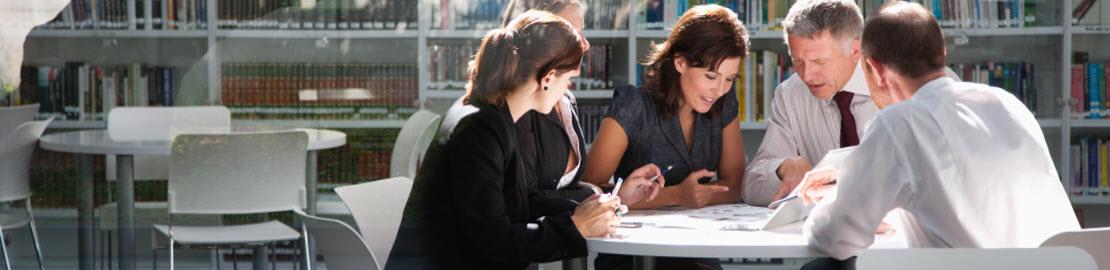 5 Personen an einem runden Tisch sitzend und diskutierend