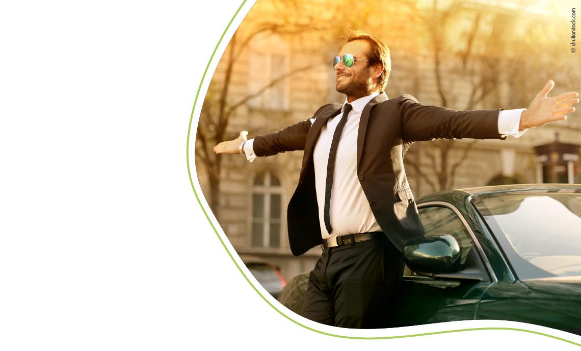 Mann mit Sonnenbrille und Anzug vor Auto