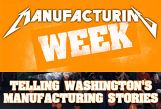Man and a woman smiling and working on a laptop.